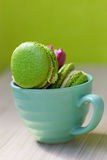 Macaroons in cup on wooden table Royalty Free Stock Images