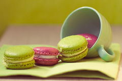 Macaroons in cup on wooden table Stock Photos