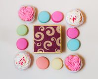 Macaroons, cupcakes and gift box on beige background Royalty Free Stock Image
