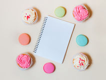 Macaroons, cupcakes and notebook on beige background Royalty Free Stock Photo