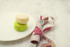 Macaroons dessert  and a measuring tape Royalty Free Stock Images