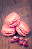 Macaroons with dry roses on retro  wooden background Royalty Free Stock Images