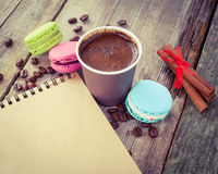 Macaroons, espresso coffee cup, cinnamon sticks and sketch book. On wooden rustic table, vintage stylized photo Royalty Free Stock Photos