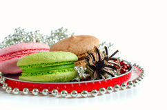 Macaroons and fir-cone. Colorful acaroons and fir-cone in round plate with chaplet Royalty Free Stock Image