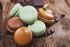 Macaroons with the flavors of coffee, pistachio, chocolate and r. Aspberries presented on a piece of wood Stock Image