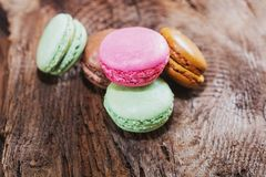 Macaroons with the flavors of coffee, pistachio, chocolate and r. Aspberries presented on a piece of wood Stock Photography