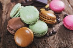 Macaroons with the flavors of coffee, pistachio, chocolate and r. Aspberries presented on a piece of wood Stock Photo