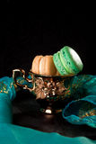 Macaroons in  gold vintage cup, on black and green background. French dessert. Royalty Free Stock Image