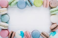 Macaroons or macaron on a white wooden background, almond cookies in the form of decoration, copy space.  Stock Image