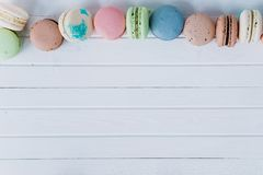 Macaroons or macaron on a white wooden background, almond cookies on a white desk, copy space.  Stock Photos