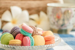 Macaroons. Macarons in a dish with flowers on green grass backgrounds,soft focus Stock Photo