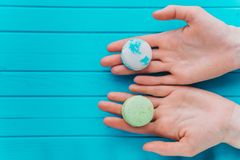 Macaroons or macarons lie in female hands on a turquoise background. Top view, copy space.  Stock Photography