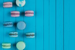 Macaroons or macarons in pastel colors lie in staggered order on a blue wooden background on the left, copy space.  Stock Photos