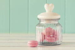 Macaroons (macarons). Some delicious pink macarons in a glass jar on a white wooden table with a robin egg blue background. Vintage Style Stock Image