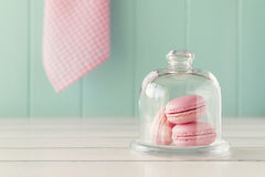 Macaroons (macarons). Some macarons in a glass bell jar on a white wooden table with a robin egg blue background and a pink checkered napkin. Vintage Style Stock Images