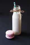 Macaroons and milk in a bottle with striped straws Stock Images