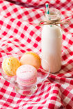 Macaroons and milk in a bottle with striped straws stock photo