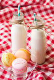 Macaroons and milk in a bottle with striped straws stock image