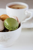 Macaroons och kopp av tea Arkivbilder