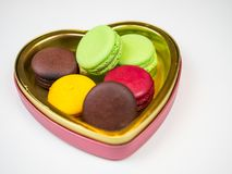 Macaroons in opening golden heart shape box, colorful dessert on white background Royalty Free Stock Photos