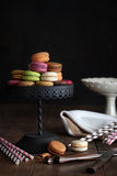 Macaroons på cakestand med mörk bakgrund Arkivfoto