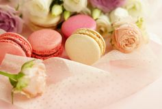 Macaroons in pastel colors with flowers on a pale pink background.Holiday background. Copy space royalty free stock photo