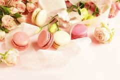 Macaroons in pastel colors with flowers on a pale pink background.Holiday background. Copy space stock photography