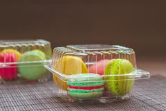 Macaroons in the plastic box. Two plastic boxes with macaroons on the table on dark background Stock Photos