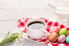 Macaroons on a plate with snowdrops and a cup of coffee stock photos