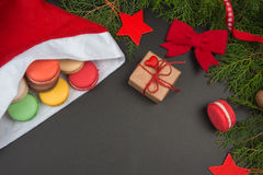 Macaroons in Santa Claus hat on black chalkboard. Christmas background Royalty Free Stock Photography