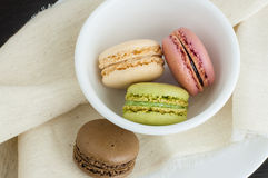 Macaroons in a small white bowl. On a linen tablecloth, close up royalty free stock images