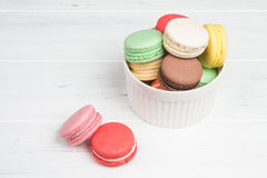 Macaroons in white ceramic bowl on wooden table. Bright dessert Stock Photo