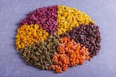 Macarrão colorido da forma incomum com as tinturas vegetais naturais, alinhado em um círculo close up do fundo foto de stock