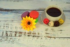 Macarrones, café, baals y flor en una tabla imagen de archivo
