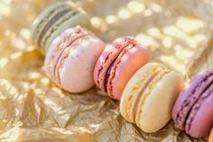 Macarrones coloreados franceses dulces en un papel de oro y una tabla de madera Dulces deliciosos para el t? fotos de archivo