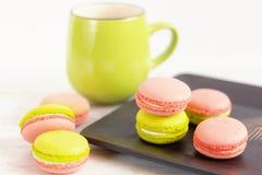 Macarrones coloridos del verde y del rosa con la taza verde Imagen de archivo libre de regalías