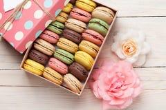 Macarrones coloridos en una caja y rosas de regalo Fotografía de archivo