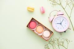 Macarrones coloridos y flores color de rosa con la caja de regalo en tabl de madera fotografía de archivo libre de regalías