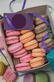 Macarrones coloridos y flores color de rosa en la tabla de madera Macarons dulces en caja de regalo Visión superior Imagen de archivo libre de regalías