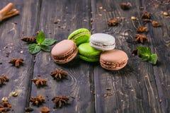 macarrones con el relleno de la baya, la crema del chocolate y el turrón en un soporte de madera imagen de archivo libre de regalías