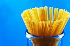Macarrones crudos de los espaguetis de las pastas en fondo azul Imagenes de archivo