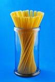 Macarrones crudos de los espaguetis de las pastas en fondo azul Imagen de archivo libre de regalías