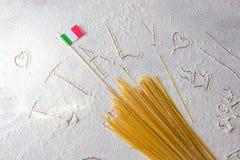 Macarrones crudos de los espaguetis de las pastas y bandera italiana en fondo blanco floured Fotografía de archivo libre de regalías