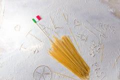 Macarrones crudos de los espaguetis de las pastas y bandera italiana en fondo blanco floured Foto de archivo