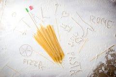 Macarrones crudos de los espaguetis de las pastas y bandera italiana en fondo blanco floured Concepto italiano de la cocina del v Foto de archivo libre de regalías