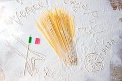 Macarrones crudos de los espaguetis de las pastas y bandera italiana en la tabla floured Palabras Venecia, Roma y pastas escritas Foto de archivo