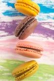 Macarrones de las galletas del color con un fondo con las acuarelas, colores brillantes, arte de cocinar, fondo brillante fotos de archivo