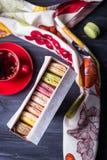 Macarrones deliciosos en té de la caja y de la fruta de regalo en fondo de madera oscuro Visión superior Imagen de archivo libre de regalías
