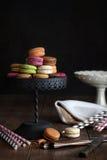 Macarrones en soporte de la torta con el fondo oscuro Foto de archivo