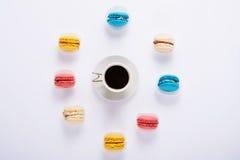 macarrones multicolores alrededor y café en el fondo blanco de Imagen de archivo